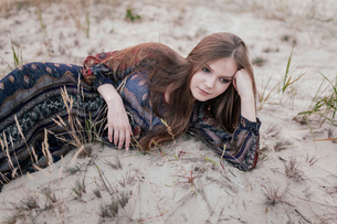 girl lying on the sand, leaning on the armの写真素材 [FYI03757852]