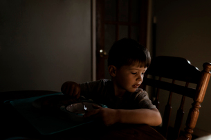 Boy sitting at a kitchen table having breakfast in the morningの写真素材 [FYI03758798]