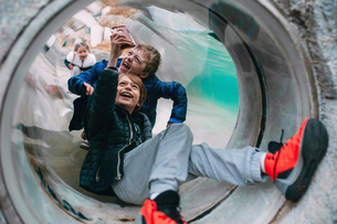 Young kids in a tunnel smiling at otter swimming at zoo in Indianaの写真素材 [FYI03758810]