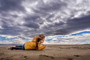 Girl in yellow jacket writes in sand on beach under big cloudy skyの写真素材 [FYI03759028]