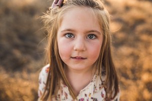Close up portrait of young girl outdoors in California fieldの写真素材 [FYI03759141]