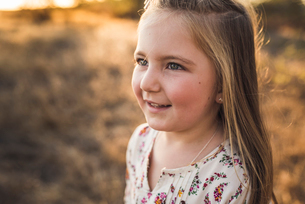 Close up portrait of young girl smiling outdoors in California fieldの写真素材 [FYI03759147]
