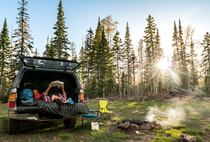 Good Spot to Read - Young woman reading wile car camping in forestの写真素材 [FYI03759244]