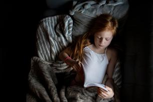 Little Redhead Girl Lying Down Reading a Bookの写真素材 [FYI03759292]