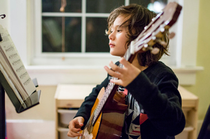 a boy studies sheet music as he practices guitarの写真素材 [FYI03759396]