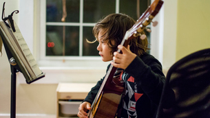 a young boy reads music and practices guitarの写真素材 [FYI03759400]