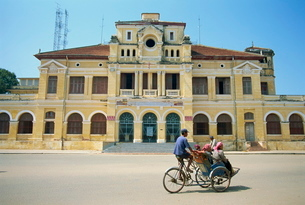 A cyclo passing the Old Post Office in Phnom Penh in Cambodia, Indochina, Southeast Asiaの写真素材 [FYI03759995]