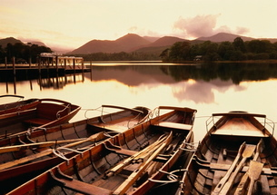 Tranquil scene at sunset over Derwentwater and Derwent Isle with pleasure boats, Keswick, Lake Distrの写真素材 [FYI03761058]