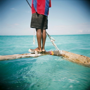 Man standing on outrigger in Indian Ocean, Zanzibar, Tanzaniaの写真素材 [FYI03761234]
