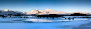 Winter view at dawn over frozen Lochain Na h'Achlaise to sun-kissed Black Mount hills, Rannoch Moorの写真素材 [FYI03761334]