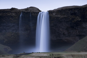 Seljalandsfoss Waterfall captured at dusk using long exposure to record movement in the water, nearの写真素材 [FYI03761361]