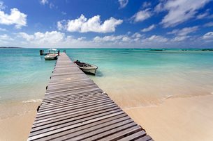 Wooden jetty with boats tied to it stretching out into the Indian Ocean off an idyllic beach on Ileの写真素材 [FYI03761404]