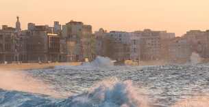 Buildings along The Malecon bathed in soft evening sunlight with large waves crashing against the seの写真素材 [FYI03761423]