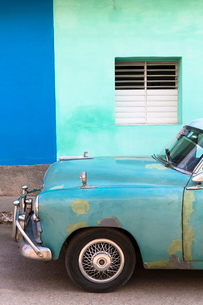 Vintage American car parked in front of the green and blue walls of a colonial building, Trinidad, Sの写真素材 [FYI03761439]