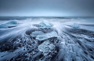Jokulsa Beach on a stormy day, where icebergs from nearby Jokulsarlon glacial lagoon flow into the Nの写真素材 [FYI03761450]