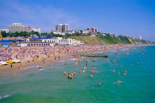 Holidaymakers in the sea and on the beach, Bournemouth, Dorsetの写真素材 [FYI03762162]