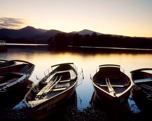 Boats moored beside Derwent Water at dusk, Lake District, Cumbriaの写真素材 [FYI03762370]