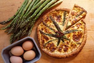 Overhead shot of asparagus quiche, a French vegetarian dish, with eggs and raw fresh asparagusの写真素材 [FYI03762736]