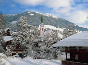 Snow covers the village and church of Alpbach in the Tyrol in the winter, Austriaの写真素材 [FYI03762860]