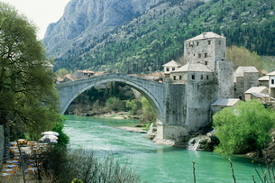 The Turkish Bridge over the River Neretva dividing the town, Mostar, Bosnia, Bosnia-Herzegovinaの写真素材 [FYI03762987]