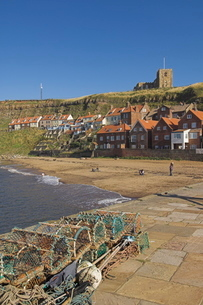 Whitby church, sandy beach and lobster pots on quayside, Whitby, North Yorkshire, Yorkshireの写真素材 [FYI03765225]