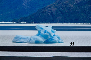 Hikers walking in front of a floating iceberg, Lake Gray, Torres del Paine National Parkの写真素材 [FYI03765714]