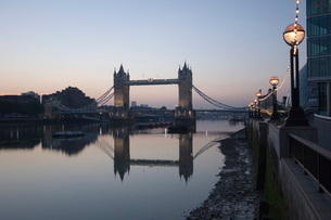 Tower Bridge reflected in the calm water of the River Thames in the early morning, viewed from the Sの写真素材 [FYI03766340]