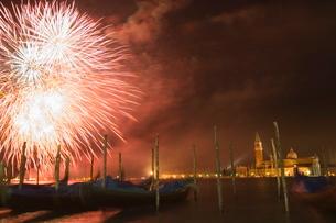 Carnival fireworks, gondolas on waterfront at night, San Giorgio Maggiore, Venice, Venetoの写真素材 [FYI03767254]