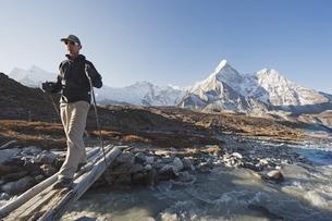 Trekker crossing a mountain stream, Ama Dablam, 6812m, Solu Khumbu Everest Region, Sagarmatha Nationの写真素材 [FYI03767693]