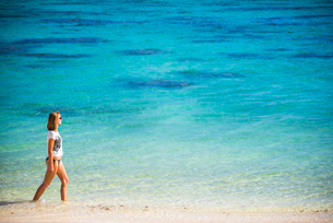 Woman walking along a tropical beach, Rarotonga Island, Cook Islands, South Pacificの写真素材 [FYI03769522]