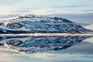 Snow-capped mountains reflected in the calm waters of Olga Strait, Svalbard, Arctic, Norway, Scandinの写真素材 [FYI03770380]