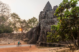 Bicycle going through the South Gate in Angkor Thom at sunrise, Angkor, Siem Reap Province, Cambodiaの写真素材 [FYI03770458]