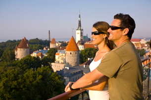 A couple take in the views of lower Old Town with Oleviste Church in the background, Tallinn, Estoniの写真素材 [FYI03771112]