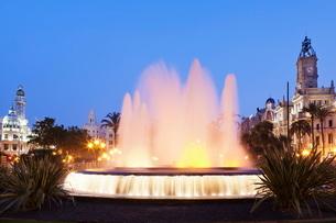 Illuminated fountain on Plaza del Ayuntamineto with town hall at dusk, Valencia, Comunidad Valenciaの写真素材 [FYI03772535]