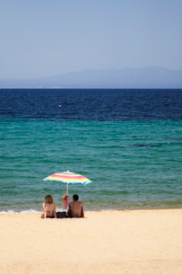 Couple under a parasol at the beach of Porto Puddu, Sardiniaの写真素材 [FYI03772537]