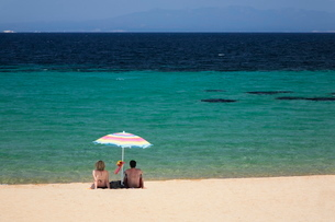 Couple under a parasol at the beach of Porto Puddu, Sardiniaの写真素材 [FYI03772540]