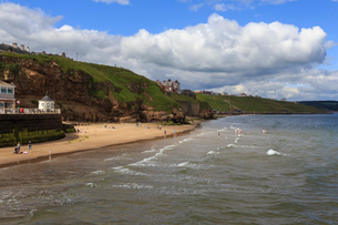 Bathers on West Cliff Beach, backed by grassy cliffs in summer, Whitby, North Yorkshireの写真素材 [FYI03772621]