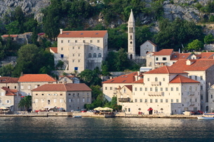 Church of Our Lady of the Rosary and a waterside restaurant lit by evening light, Perast, Bay of Kotの写真素材 [FYI03772774]
