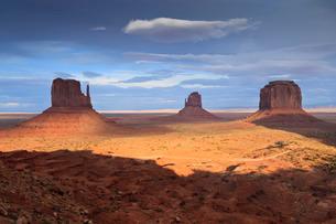 Mittens at dusk, late evening sun lights the desert floor, Monument Valley Navajo Tribal Park, Utahの写真素材 [FYI03772831]