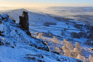 Fresh snow on Curbar and Baslow Edge with misty Derwent valley and winter trees, Peak District, Derbの写真素材 [FYI03772875]