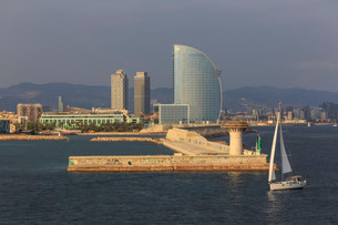 Yacht sails past La Barceloneta and the waterfront, Port Olimpic in distance, late afternoon, Barcelの写真素材 [FYI03772886]