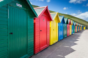 Row of colourful beach huts and their shadows with green hill backdrop, West Cliff Beach, Whitby, Noの写真素材 [FYI03772893]
