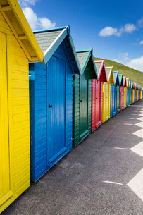 Row of colourful beach huts and their shadows with green hill backdrop, West Cliff Beach, Whitby, Noの写真素材 [FYI03772899]