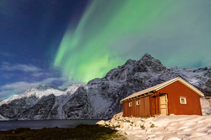 Northern Lights (aurora borealis) illuminate snowy peaks and the wooden cabin on a starry night at Bの写真素材 [FYI03773035]