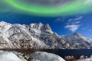 Northern Lights (aurora borealis) illuminate the snowy peaks and the blue sky during a starry night,の写真素材 [FYI03773036]