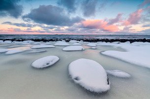 Dawn on the cold sea surrounded by snowy  rocks shaped by wind and ice at Eggum, Vestvagoy (Vest-Vagの写真素材 [FYI03773041]