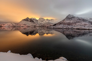 The light of the moon and snowy peaks reflected in the cold sea lit the night at Svolvaer, Lofoten Iの写真素材 [FYI03773045]