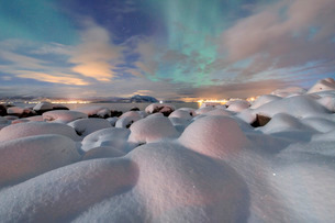 The pink light and the aurora borealis (Northern Lights) illuminate the snowy landscape on a starryの写真素材 [FYI03773046]