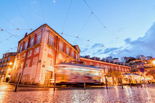 City lights on the typical architecture and old streets at dusk while the tram 28 proceeds, Alfama,の写真素材 [FYI03773048]