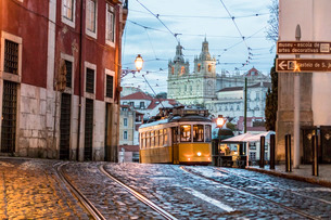 Romantic atmosphere in the old streets of Alfama with the castle in the background and tram number 2の写真素材 [FYI03773049]
